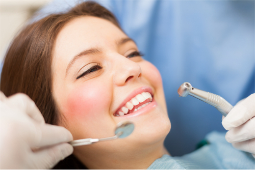 Smiling Female About To Have Her Teeth Cleaned By Dentist