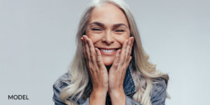 Older Female Holding Cheeks With Hands Smiling After Oral Surgery