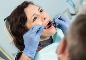 Woman Undergoing Oral Exam By A Dentist